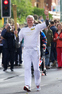 Professor Neil Gorman carrying the Olympic flame